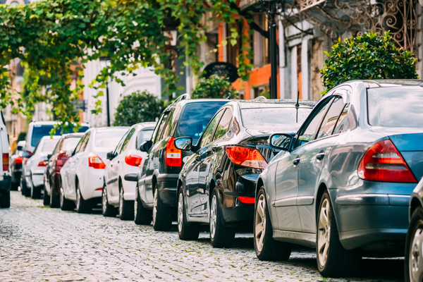 many-cars-parked-on-street-in-city-in-sunny-P752QJE-2